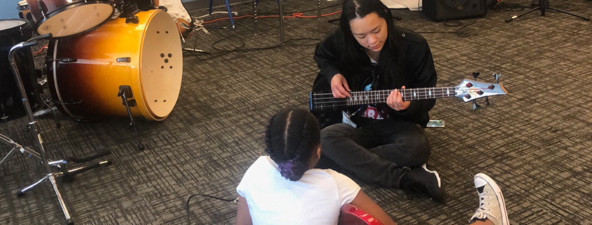 A photo of an instructor teaching a camper how to play a bass riff.
